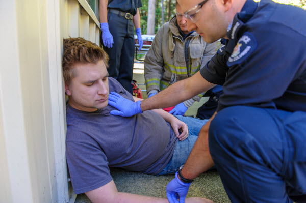 injured worker lying slumped against wall with person giving first aid.