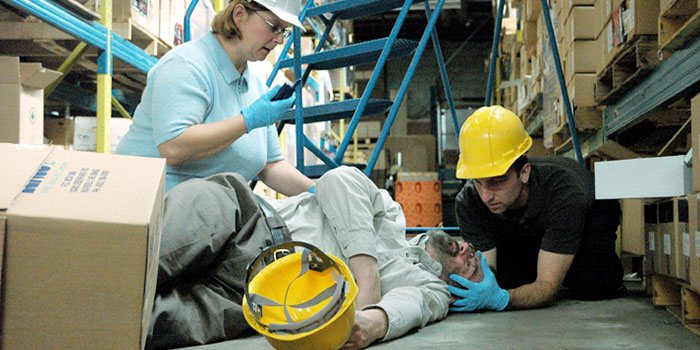 workers providing first aid to injured co-worker