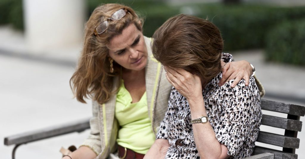 Psychological First Aid Training Can Save Lives - Image of two people sitting on a park bench with one comforting the other.