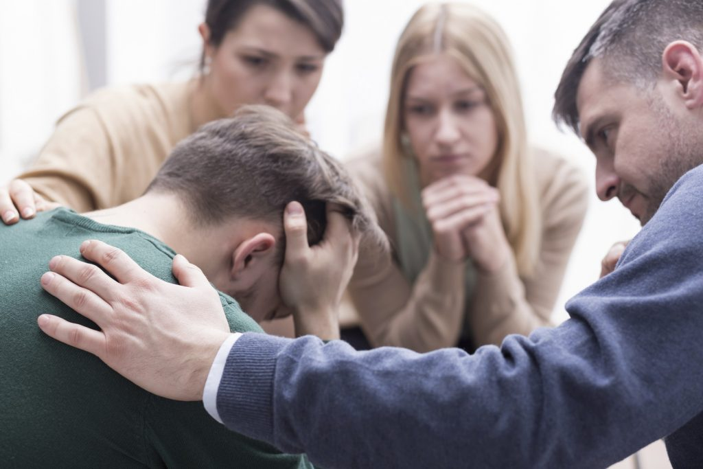 Psychological First Aid Training Can Save Lives - Close-up of a devastated young man holding his head in his hands and a group of friends in a supportive pose around him