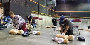 Students in first aid class doing CPR wearing face masks.