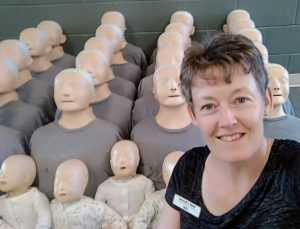 First aid instructor in foreground with CPR manikins behind